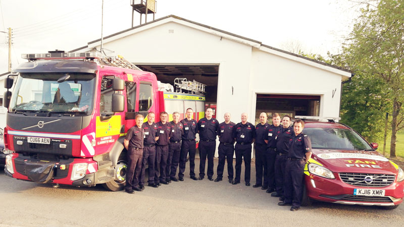 Llanwrtyd volunteer fire-fighter crew with fire engine and 4x4 co-responder vehicle in front of Fire Station in 2019.