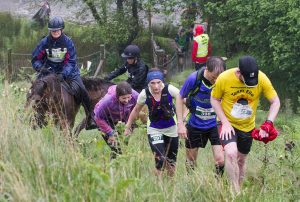 Exhausted runners pursued by horse riders