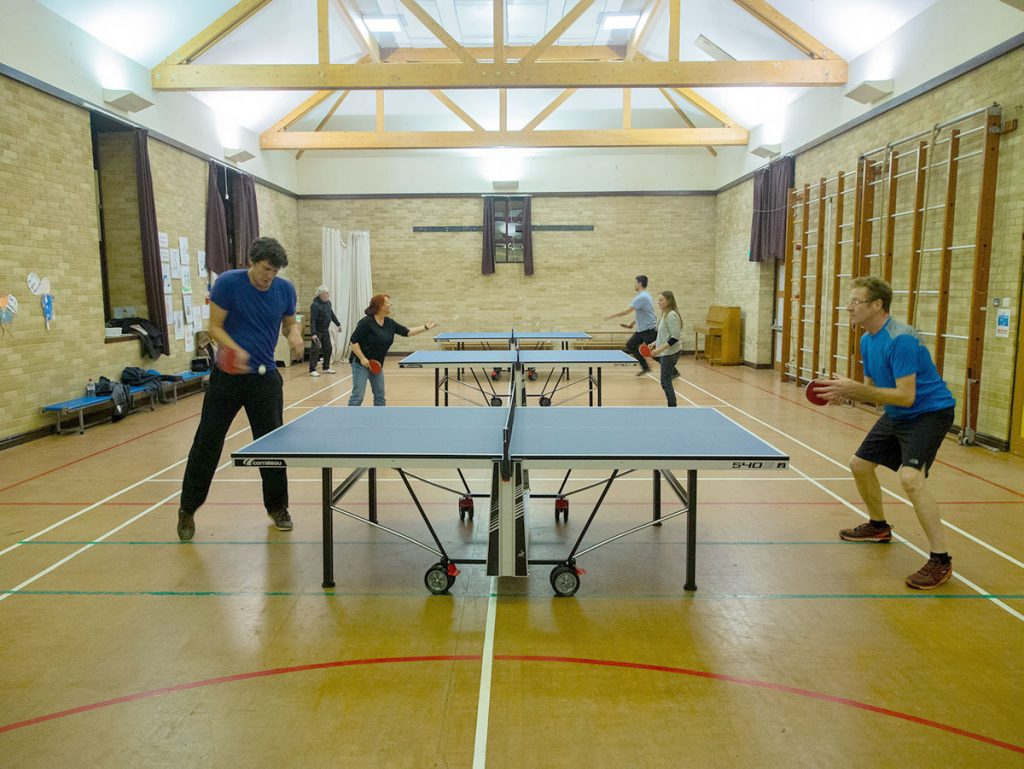 Table tennis players in Llanwrtyd Wells table tennis club in the sports hall.