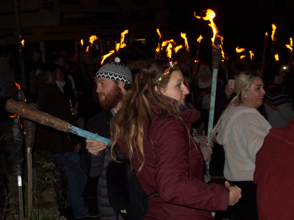 Walkers light torches to carry on the Mari Lwyd.