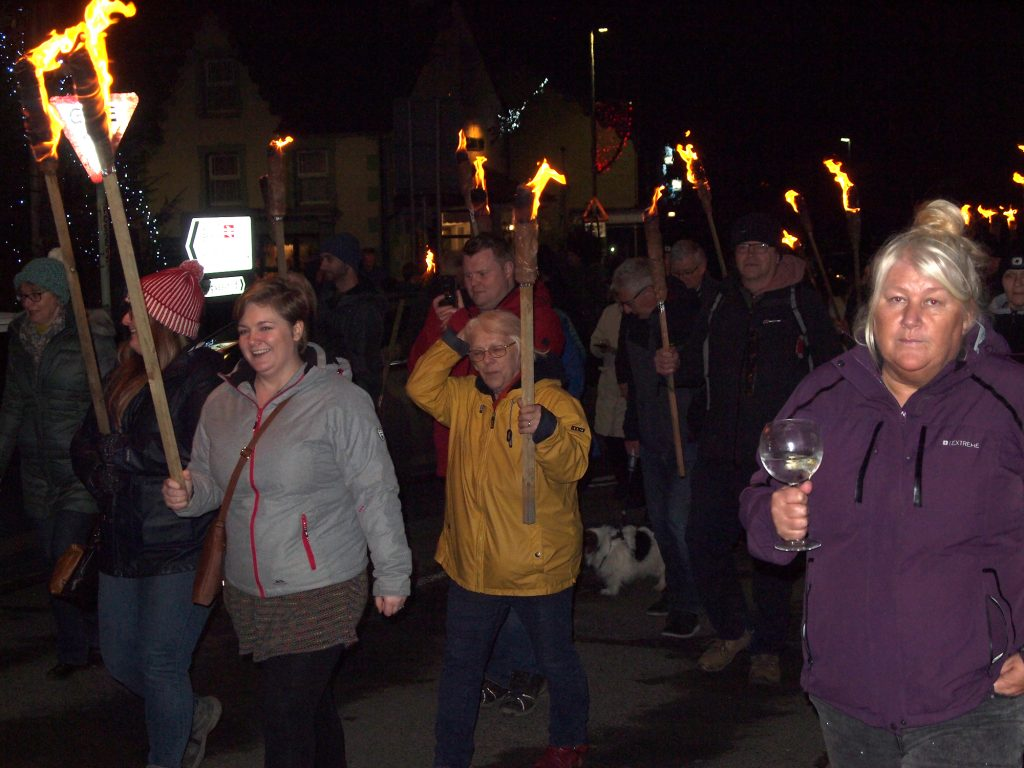 Walkers on the Mari Lwyd carry torches through the street of Llanwrtyd Wells.